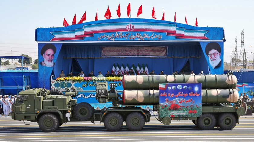 In front of portraits of supreme leader Ayatollah Ali Khamenei, right, and late revolutionary founder Ayatollah Khomeini, a long-range missile system is displayed by Iran's army during a military parade held just outside Tehran on Sept. 21.