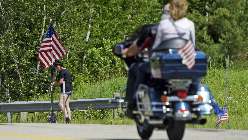 A motorcycle passes as a woman leaves flowers at the scene of a fatal accident on Route 2 in Randolp