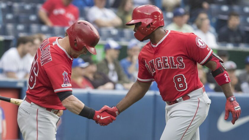 Los Angeles Angels' Justin Upton (8) is greeted by teammate Kole Calhoun after hitting a home run ag