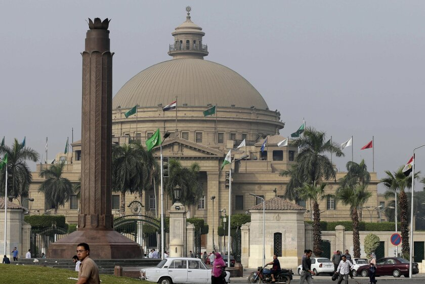 """FILE - In this Oct. 8, 2014 file photo, Egyptians walk outside Cairo University in Cairo, Egypt. Egyptian authorities are increasingly harassing foreign academics with a slew of restrictions, visa denials and deportations, especially those researching anything related to Egypt's """"revolution"""" or soc"""