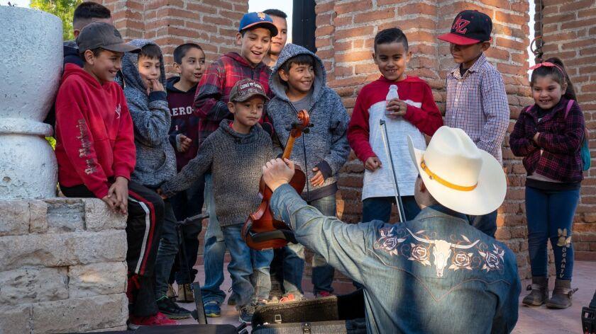 Los Cenzontles Cultural Arts Academy violinist and singer Nesta Velazquez shows off his violin to yo