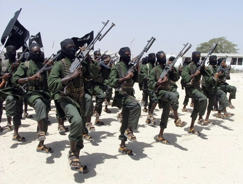 FILE - In this Thursday, Feb. 17, 2011 file photo, hundreds of newly trained al-Shabab fighters perform military exercises in the Lafofe area some 18km south of Mogadishu, in Somalia. A number of Kenyan police are missing after suspected al-Shabab gunmen attacked their vehicles near Somalia's border, injuring other officers and burning cars, police said on Tuesday, May 26, 2015. (AP Photo/Farah Abdi Warsameh, File)