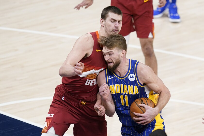 Indiana Pacers' Domantas Sabonis (11) goes to the basket against Denver Nuggets' Nikola Jokic (15) during the first half of an NBA basketball game, Thursday, March 4, 2021, in Indianapolis. (AP Photo/Darron Cummings)