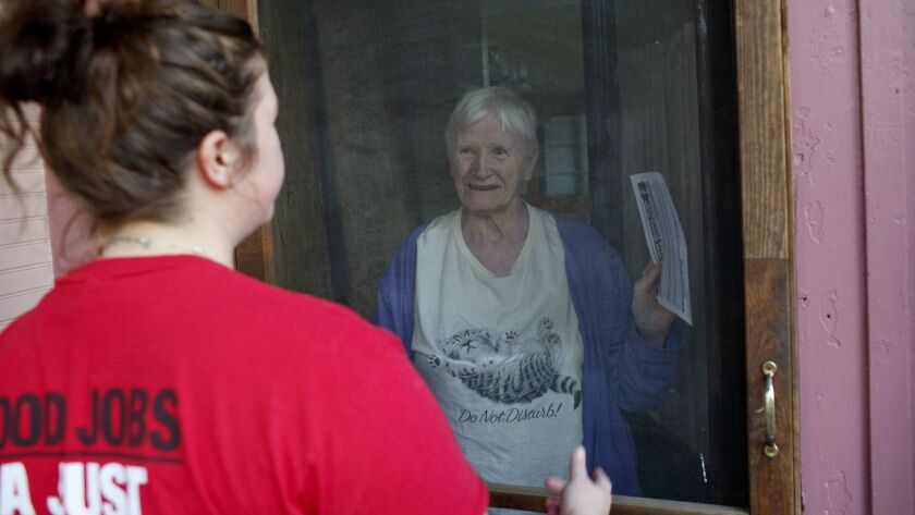 Helen Kent, 82, listens to Working America canvasser Jaclyn McCann, 28, left, as they discuss the Mi