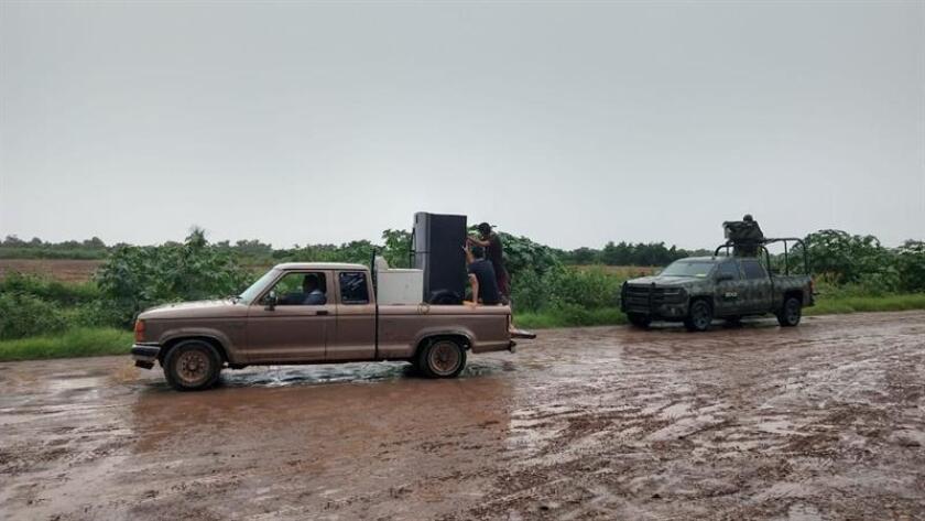 Una familia se desplaza este sábado fuera de la zona que registra afectaciones en la ciudad de Culiacán, Sinaloa (México), por el paso de la tormenta tropical Ivo. EFE/Juan Carlos Cruz