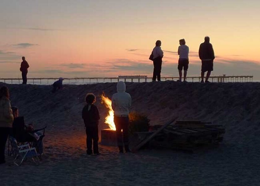 A family bids farewell to its Christmas tree in an Ocean Beach fire ring at the first sunset of 2010.