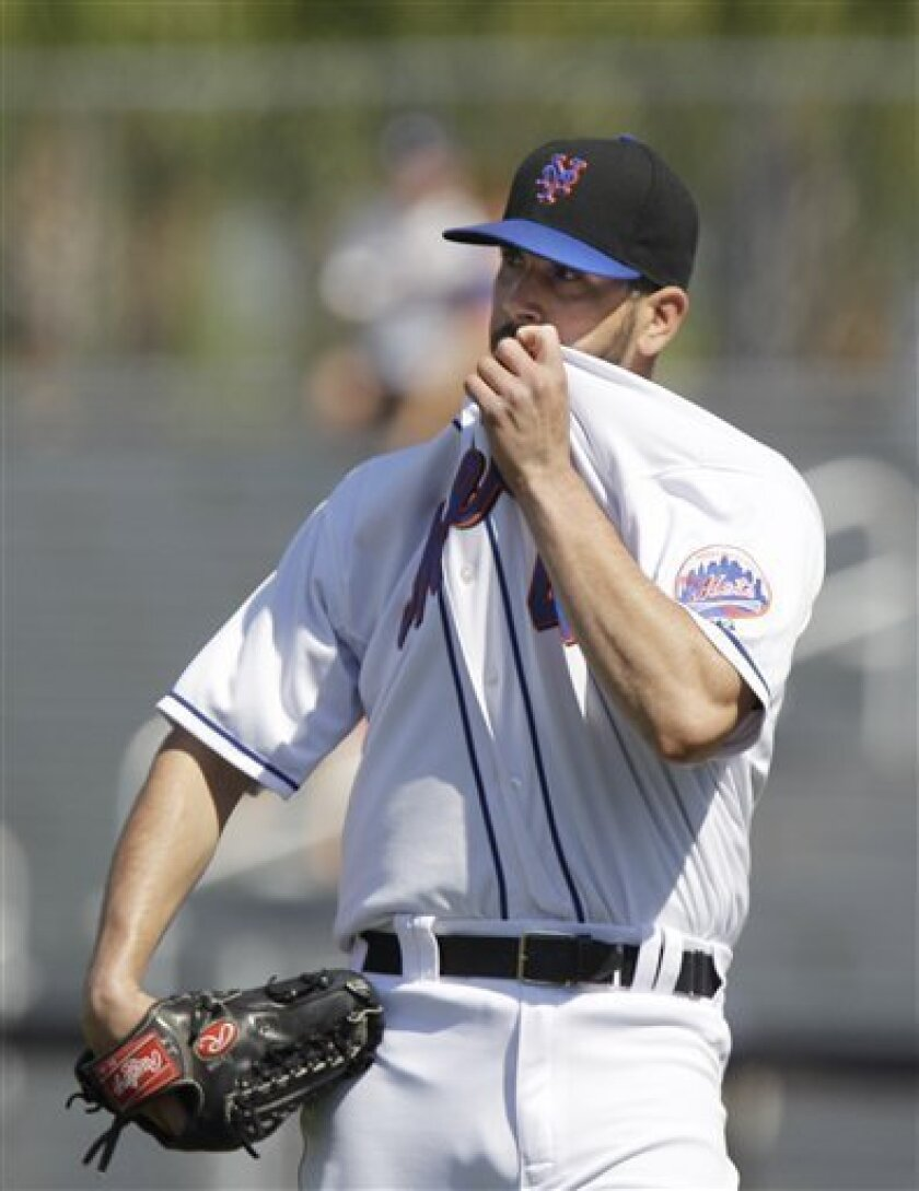 New York Mets pitcher Oliver Perez (46) wipes his face after giving up his second home run during the seventh inning of a spring training baseball game against the Washington Nationals, Saturday, March 19, 2011 in Port St. Lucie, Fla. (AP Photo/Carlos Osorio)