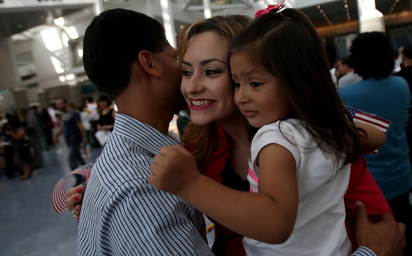 Lizbeth Lopez, a native of Mexico, gets a hug from husband Eleseo Lopez and their daughter, Damaris, 2, after getting her American citizenship at a naturalization ceremony at the Los Angeles Convention Center.