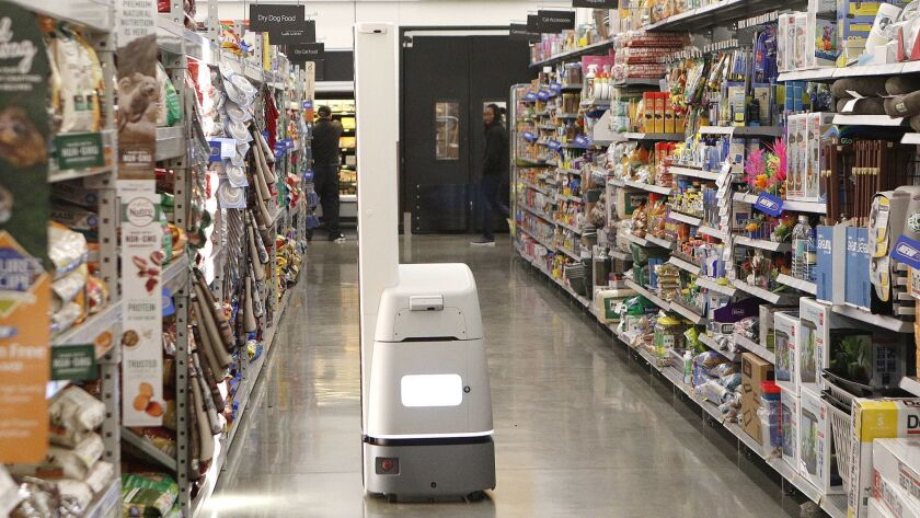 A new Bossanova robot rolls down an aisle at Walmart in Burbank on Wednesday, March 21, 2018. The ro