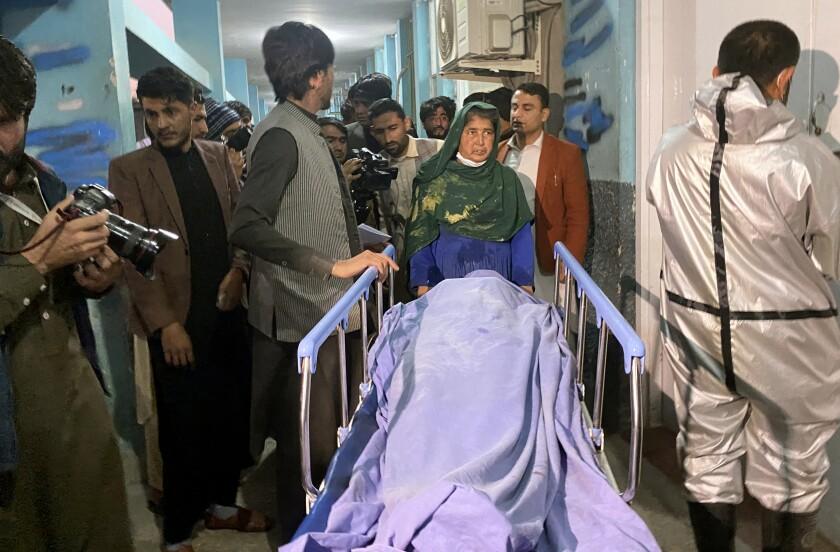 Varias personas junto al cadáver de una mujer asesinada por hombres armados en la ciudad de Jalalabad, Afganistán, el martes 2 de marzo de 2021. Tres mujeres que trabajaban para una estación privada de radio y televisión en el este de Afganistán fueron asesinadas a disparos el martes en ataques separados, informó el editor de noticias de la estación. (AP Foto/Sadaqat Ghorzang)