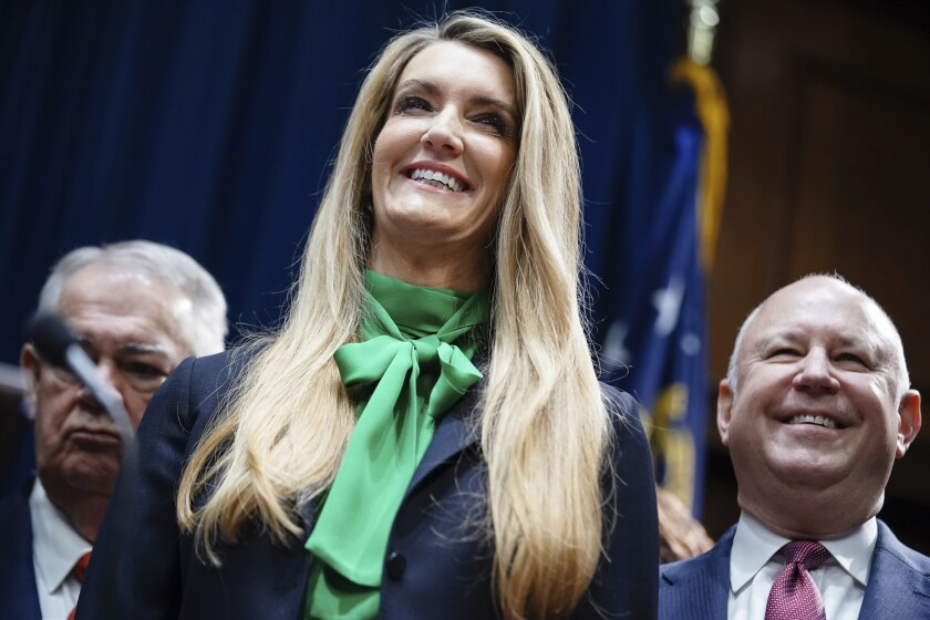 FILE - In this Wednesday, Dec. 4, 2019 file photo, businesswoman Kelly Loeffler smiles while being introduced by Georgia Gov. Brian Kemp as his pick to fill Georgia's vacant U.S. Senate seat at the Georgia State Capitol in Atlanta. Loeffler, a wealthy Republican businesswoman set to be sworn in on Monday, Jan. 6, 2020 as Georgia's next U.S. senator will enter the chamber with a unique distinction: Her first vote could be on whether to remove the president. (AP Photo/Elijah Nouvelage, File)