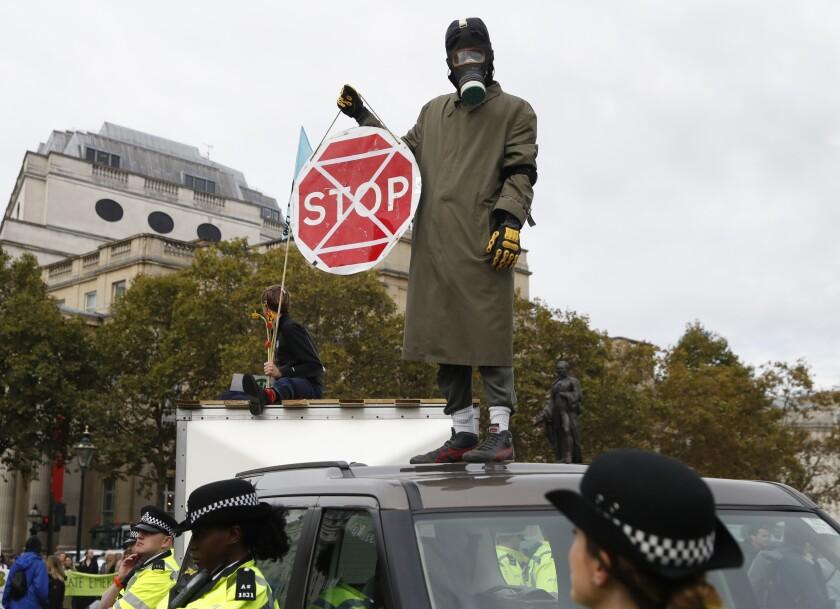 A man in a gas mask is among demonstrators blocking London's Trafalgar Square on Monday.