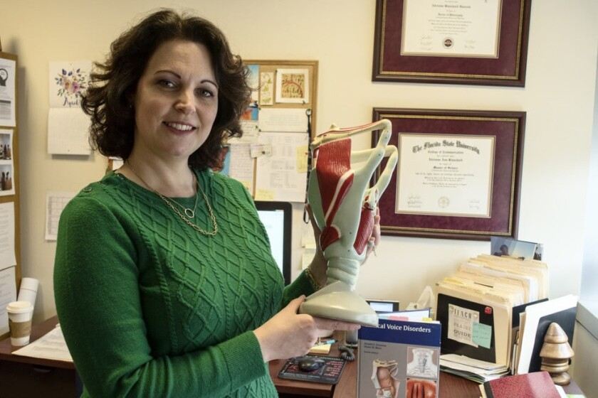 Speech pathologist Adrienne Hancock with a model of the vocal tract at George Washington University.