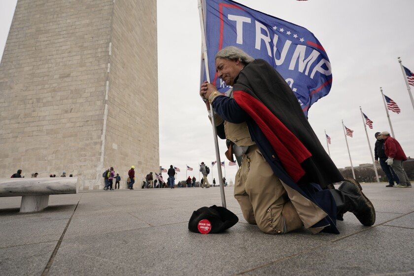 A man kneels by the Washington Monument