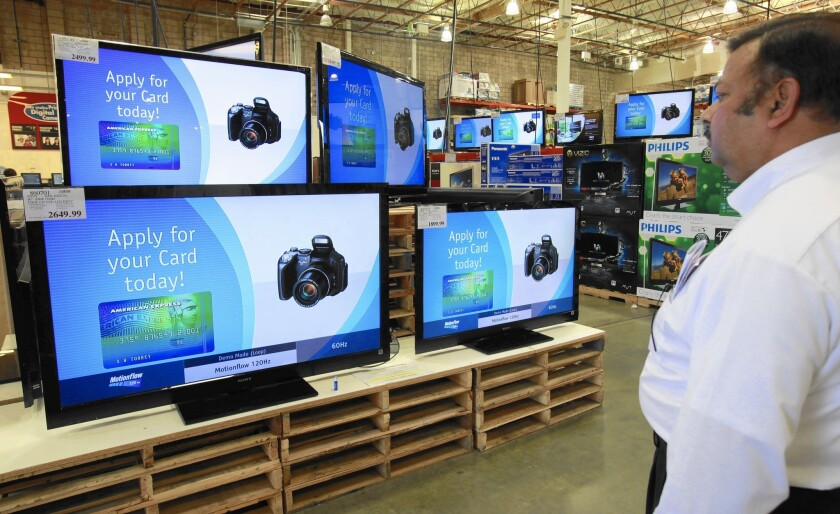 A customer looks at wide-screen TV sets advertising American Express cards at a Costco store in Mountain View, Calif., in 2010.