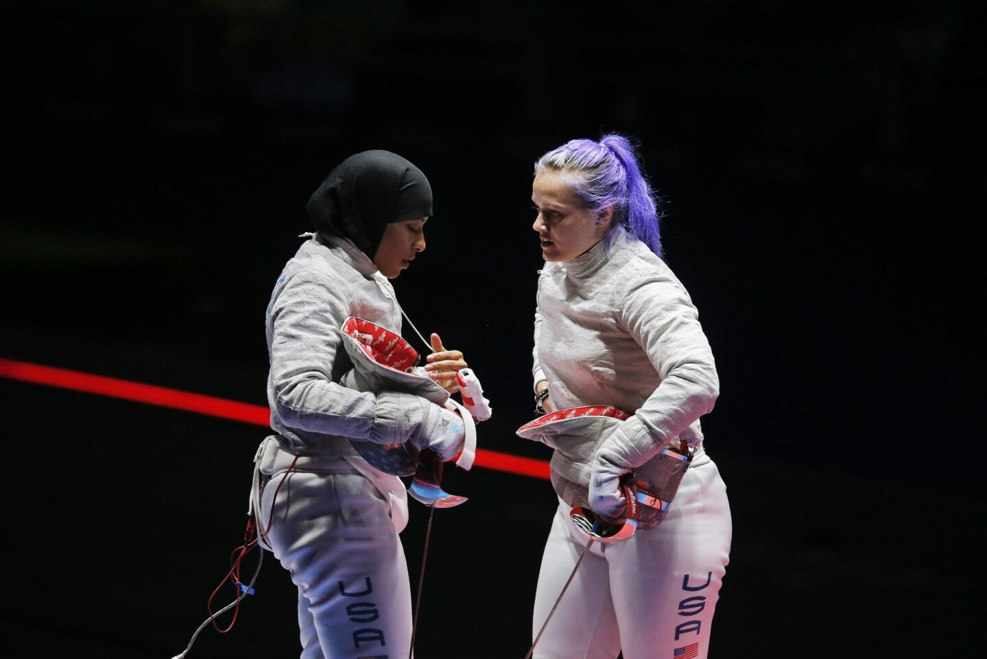 Dagmara Wozniak (R) and Ibtihaj Muhammad (L) of the USA react during the women's Sabre Team bronze medal match against Italy at the Rio 2016 Olympic Games Fencing events at the Carioca Arena 3 in the Olympic Park in Rio de Janeiro, Brazil.