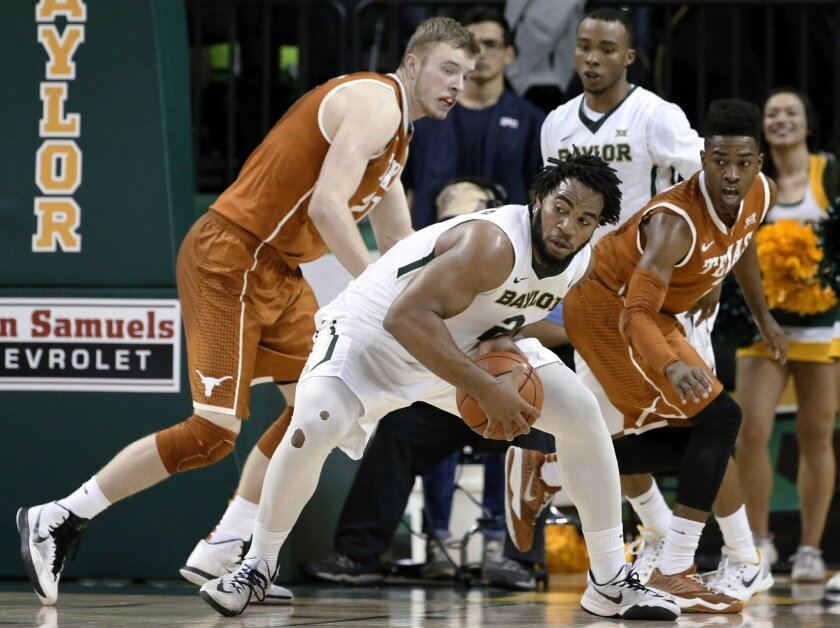 Baylor forward Rico Gathers, center, looks for a shot opportunity as Texas' Connor Lammert, left, and Isaiah Taylor, right, defend during the first half of an NCAA college basketball game, Saturday, Jan. 31, 2015, in Waco, Texas. (AP Photo/Tony Gutierrez)