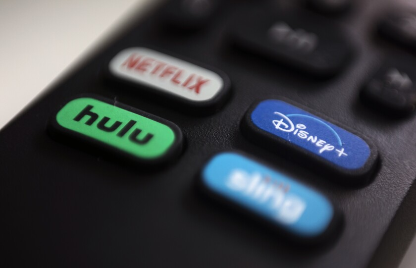 The logos for Netflix, Hulu, Disney+ and Sling TV are pictured on a remote control.
