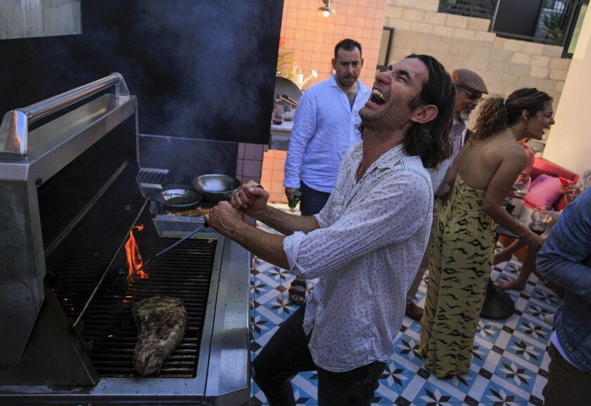 Diego Caivano entertains guests as he grills.