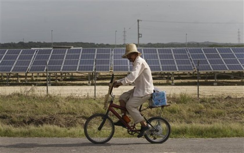 In this July 18, 2013 photo, a farmer rides past a row of solar panels in Cantarana, Cuba. The country's first solar farm opened this spring with little fanfare and no prior announcement. It boasts 14,000 photovoltaic panels which in a stroke more than doubled the country's capacity to harvest energy from the sun. (AP Photo/Franklin Reyes)