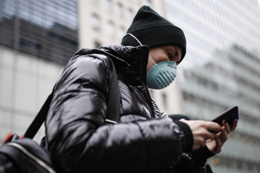 Pedestrian uses her phone while wearing a face mask in Herald Square, Thursday, March 12, 2020, in New York. New York City Mayor Bill de Blasio said Thursday he will announce new restrictions on gatherings to halt the spread of the new coronavirus in the coming days, but he hopes to avoid closing all public events such as Broadway shows. For most people, the new coronavirus causes only mild or moderate symptoms. For some it can cause more severe illness. (AP Photo/John Minchillo)