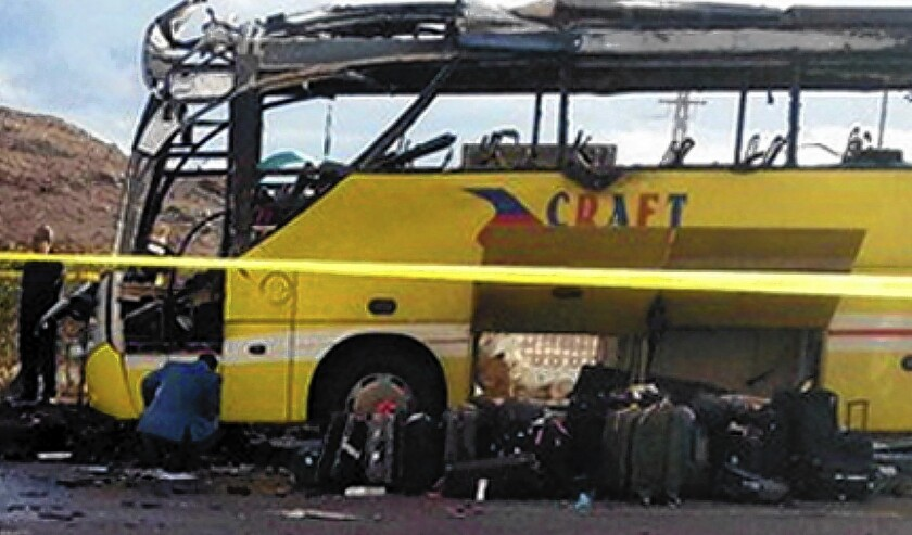 A burned-out tourist bus sits in the Egyptian Sinai resort town of Taba after a bomb went off, killing at least four people.