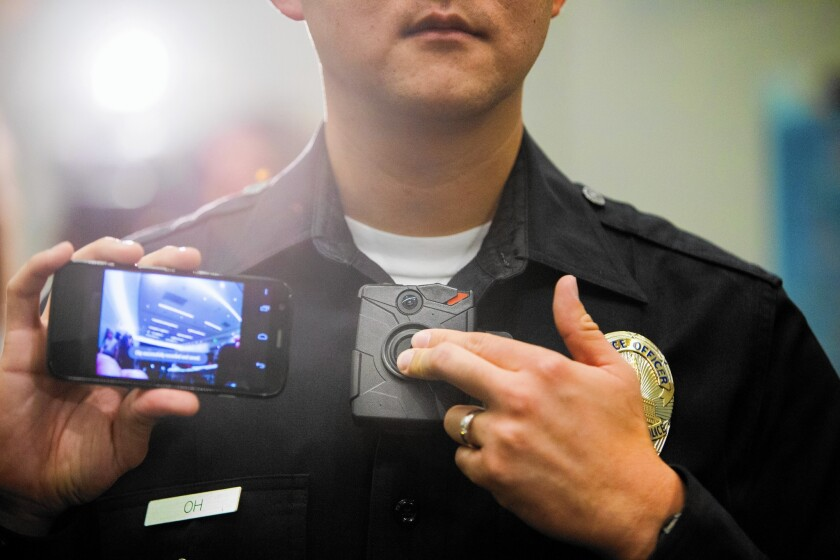 An LAPD officer holds a live-view device, left, which works with the new Taser Axon on-body police cameras. The city plans to buy 6,140 cameras and 4,400 Tasers for its officers.