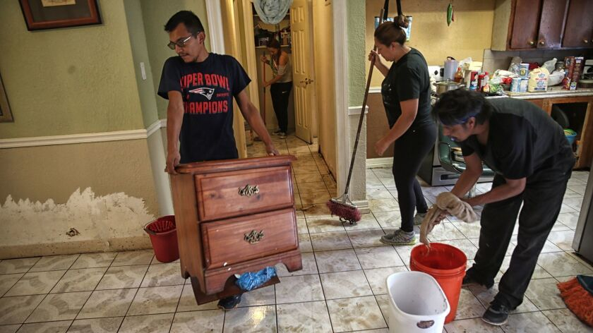 Juan Figueroa removes damaged furniture as others clean his mother's flooded northeast Houston home.