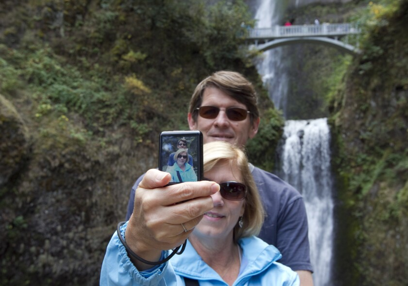 Southern Californians Randy and Lori Frith take a selfie at the Multnomah Waterfalls in the Columbia River Gorge National Scenic Area. Would they have to get a permit under proposed Forest Service regulations?