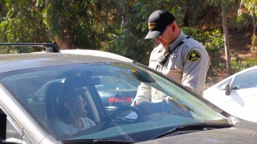 A deptuty speaks with a driver he pulled over Tuesday during the weekly rally outside Rep. Darrell I