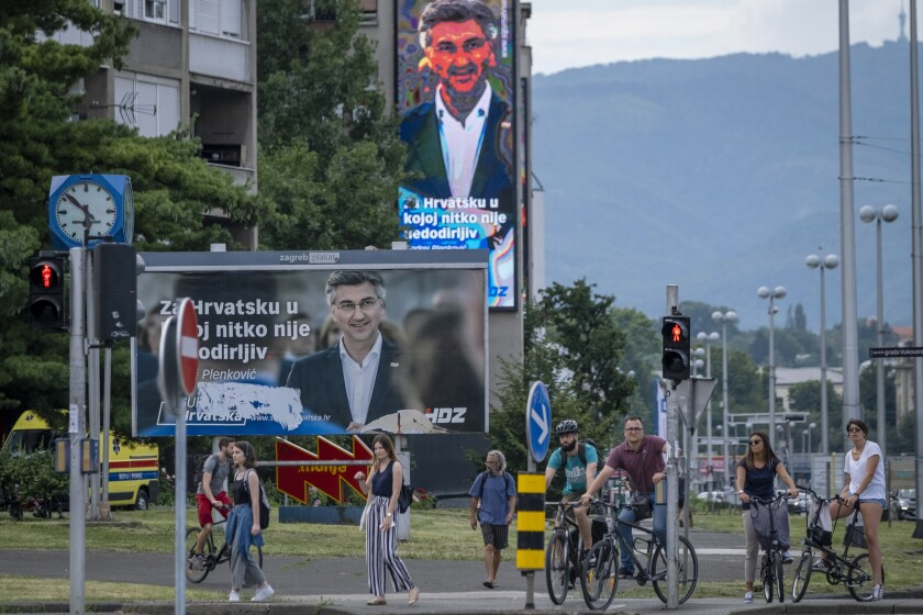 Cyclists and pedestrians wait to cross a street near the electoral posters of Prime Minister incumbent Andrej Plenkovic, in Zagreb, Croatia, Thursday, July 2, 2020. Croatia is holding a parliamentary election on July 5, 2020, with no clear winner in sight as the ruling conservatives' bid for re-election faces a strong challenge from both liberal and right-wing groups. (AP Photo/Sasa Kavic)