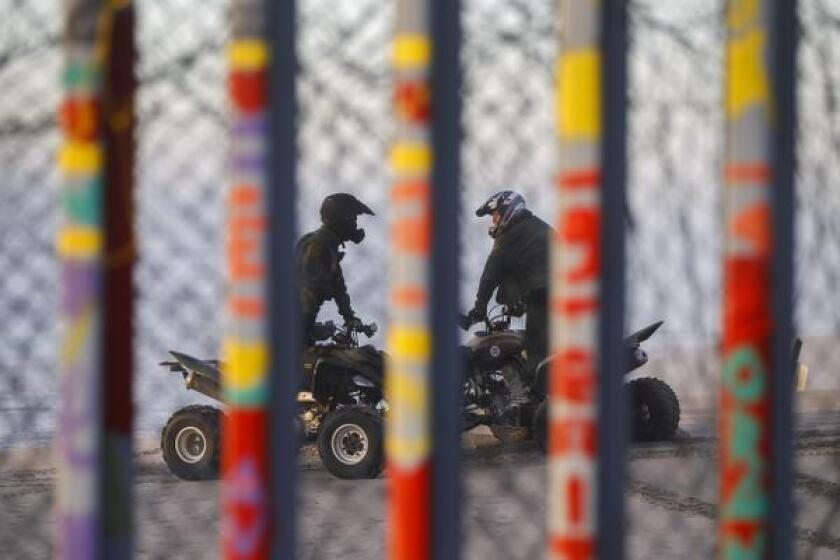Viewed through the border barrier from Plays de Tijuana, Mexico, a pair of Border Patrol agents