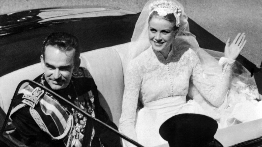 Prince Rainier III of Monaco and US actress Grace Kelly saluting the crowd as they leave Saint Nicholas' Cathedral after their wedding ceremony in Monaco.