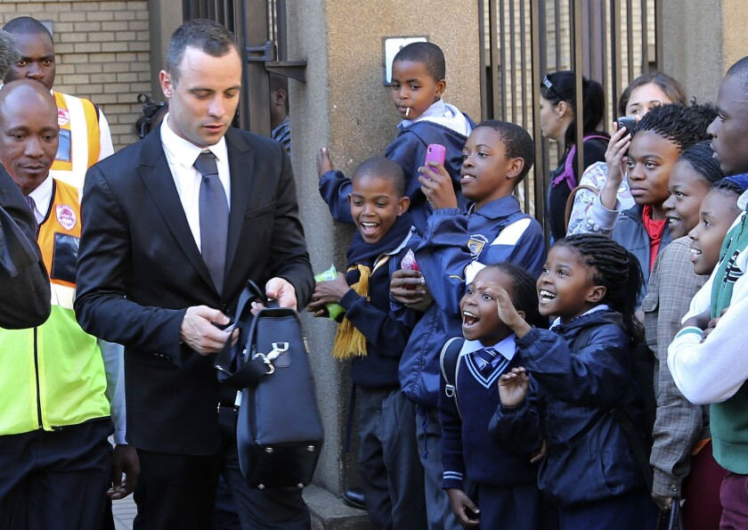 Children react as Oscar Pistorius, left, leaves the high court in Pretoria, South Africa, on Monday.
