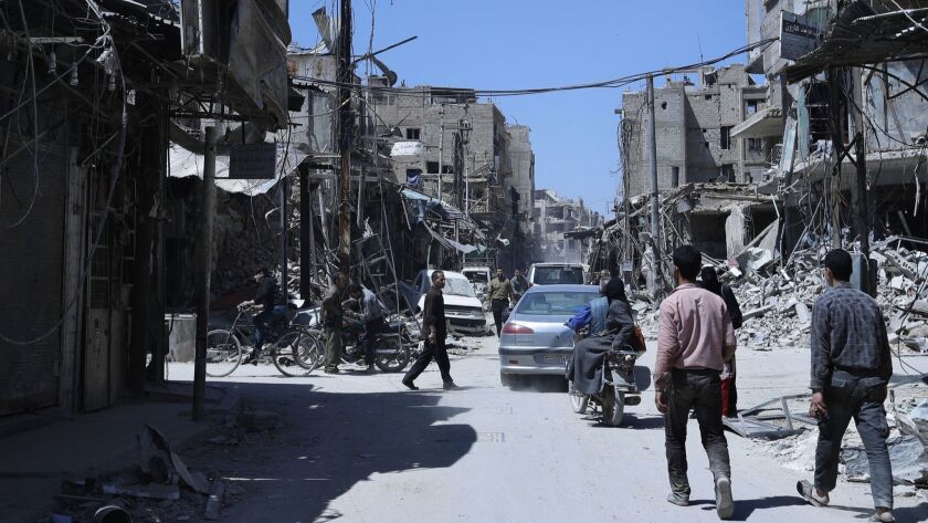 People walk among damaged buildings in the town of Douma, the site of a suspected chemical weapons a