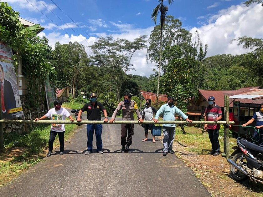 People from the Buntao community in Indonesia use a wooden barrier to block off their village. Indigenous peoples across the archipelago are locking down their villages in an effort to protect against the coronavirus.