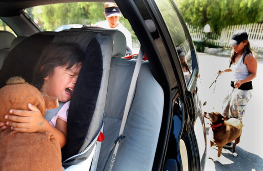 A scared Alexis Faieta cries in the back seat of the family vehicle as her parents, April and John Faieta, prepare to evacuate from Haines Canyon Avenue in Tujunga on Monday.