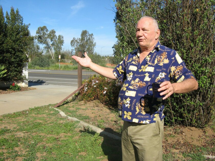 Tim Lyons, 69, gestures to the driveway of his Discovery Street home in San Marcos on Friday. A $62 million overhaul to add bridges, a levee and widen roads will lead to the loss of some of his front yard.