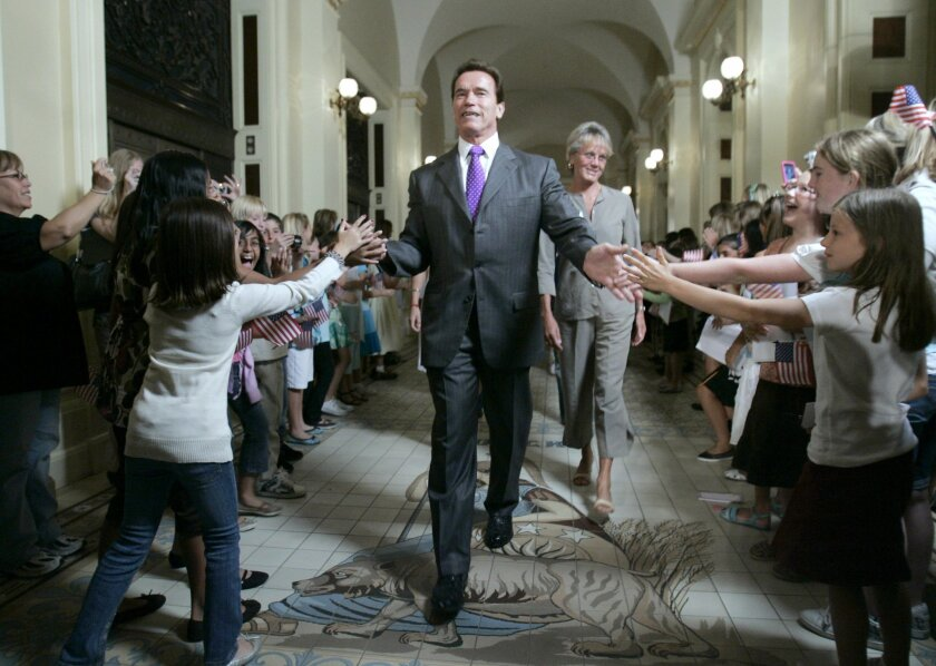 FILE -- In this Sept. 8, 2008 file photo Gov. Arnold Schwarzenegger is greeted by youngsters as he walks to a ceremony to honor several Olympic athletes from California, at the Capitol in Sacramento, Calif., Schwarzenegger is returning to the state capital Monday, Sept. 8, 2014, for two high-profile public events to discuss California's fight against climate change and unveil his official portrait at the Capitol.(AP Photo/Rich Pedroncelli, File)
