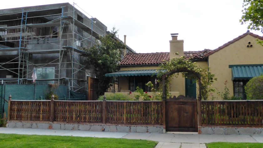 A new construction project rises next to an existing Spanish Revival house on a street in Carthay Square, a neighborhood that has applied to the L.A. city planning department to become a Historic Preservation Overlay Zone. The photo was shot last week.