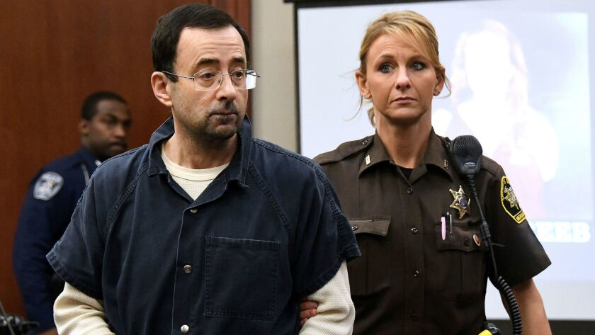Larry Nassar is escorted into the courtroom, Friday, Jan. 19, 2018, in Lansing, Mich., during the fo