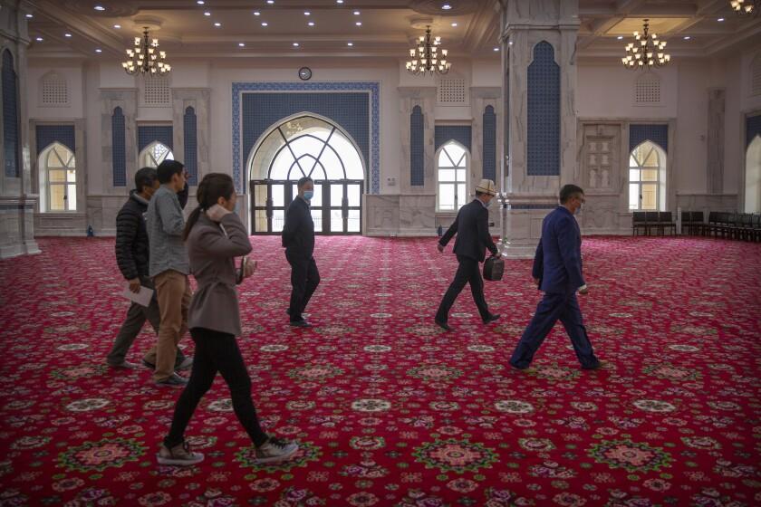 Funcionarios oficiales acompañan a periodistas extranjeros durante una visita al Instituto Islámico de Xinjiang en Urumqi, en la Región Autónoma Uigur, el 22 de abril del 2021. (AP Photo/Mark Schiefelbein)