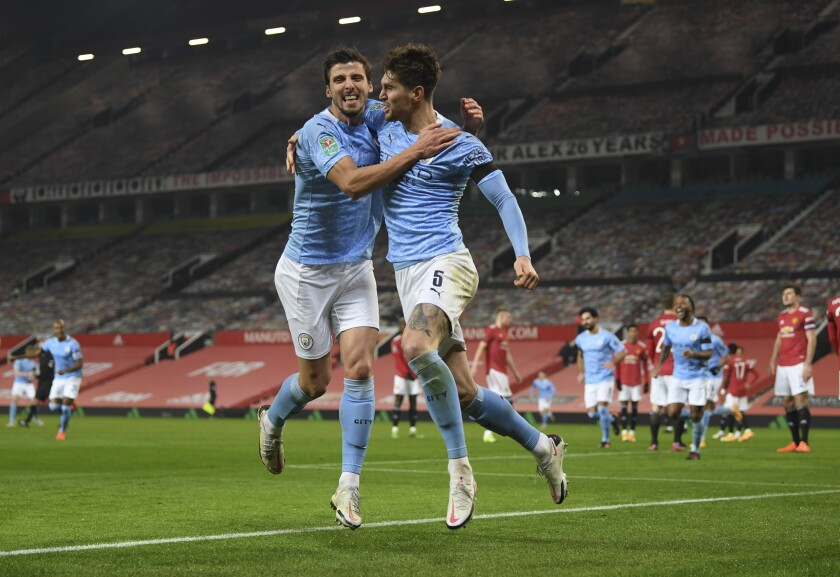 Manchester City's John Stones, right, celebrates after scoring the opening goal of his team during the English League Cup semifinal soccer match between Manchester United and Manchester City at Old Trafford in Manchester, England, Wednesday, Jan. 6, 2021. (Shaun Botterill/Pool via AP)