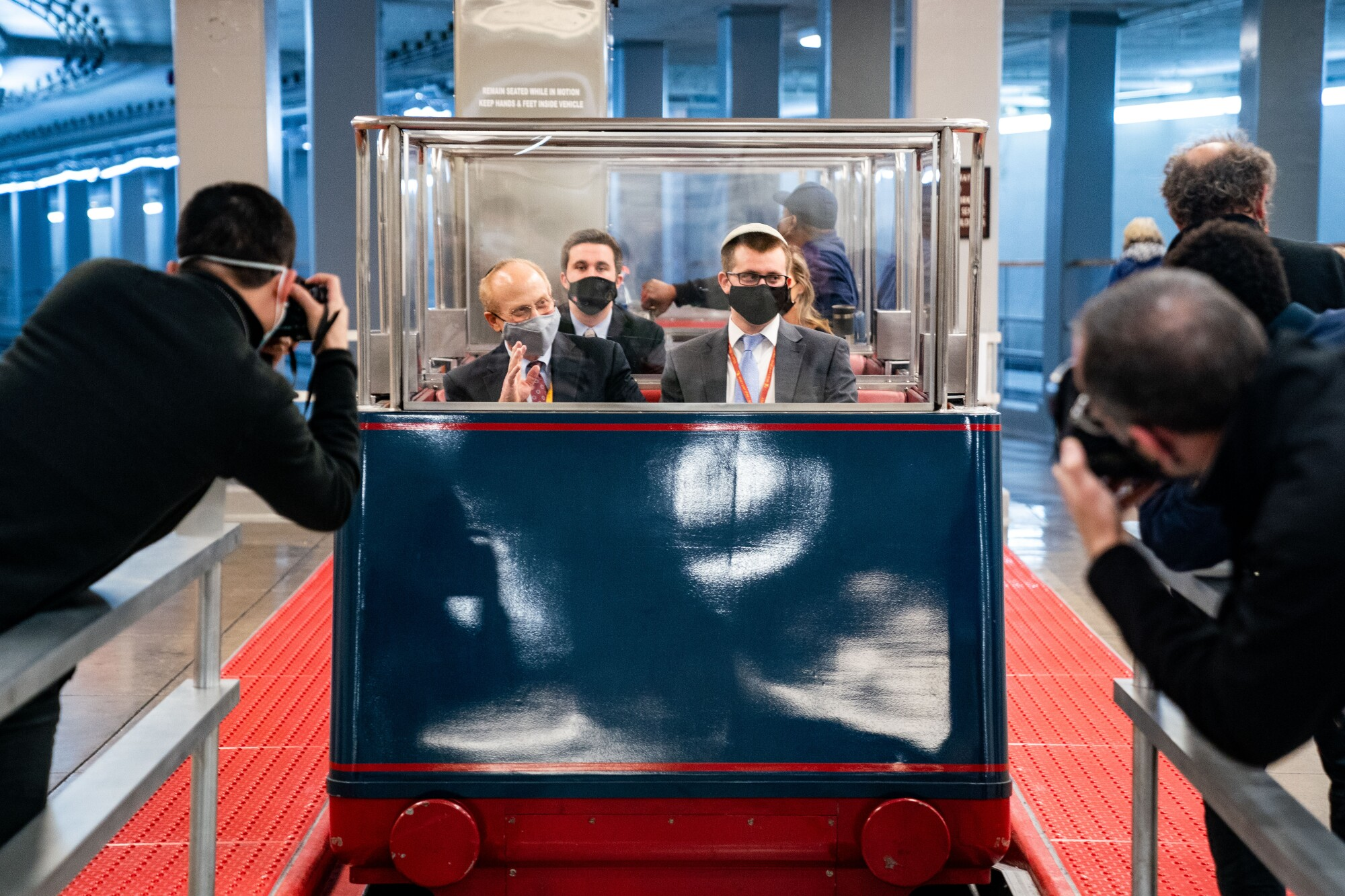 People sitting in a Senate subway car are photographed by journalists