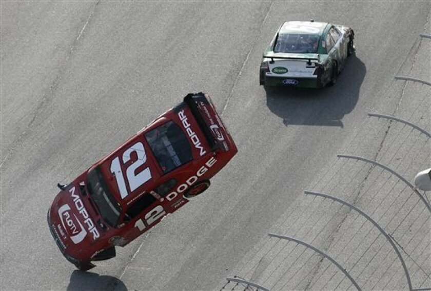 Brad Keselowski (12) flips after being nudged by Carl Edwards, top, during the NASCAR Sprint Cup Series Kobalt Tools 500 auto race at Atlanta Motor Speedway in Hampton, Ga., Sunday, March 7, 2010. (AP Photo/Joe Sebo)