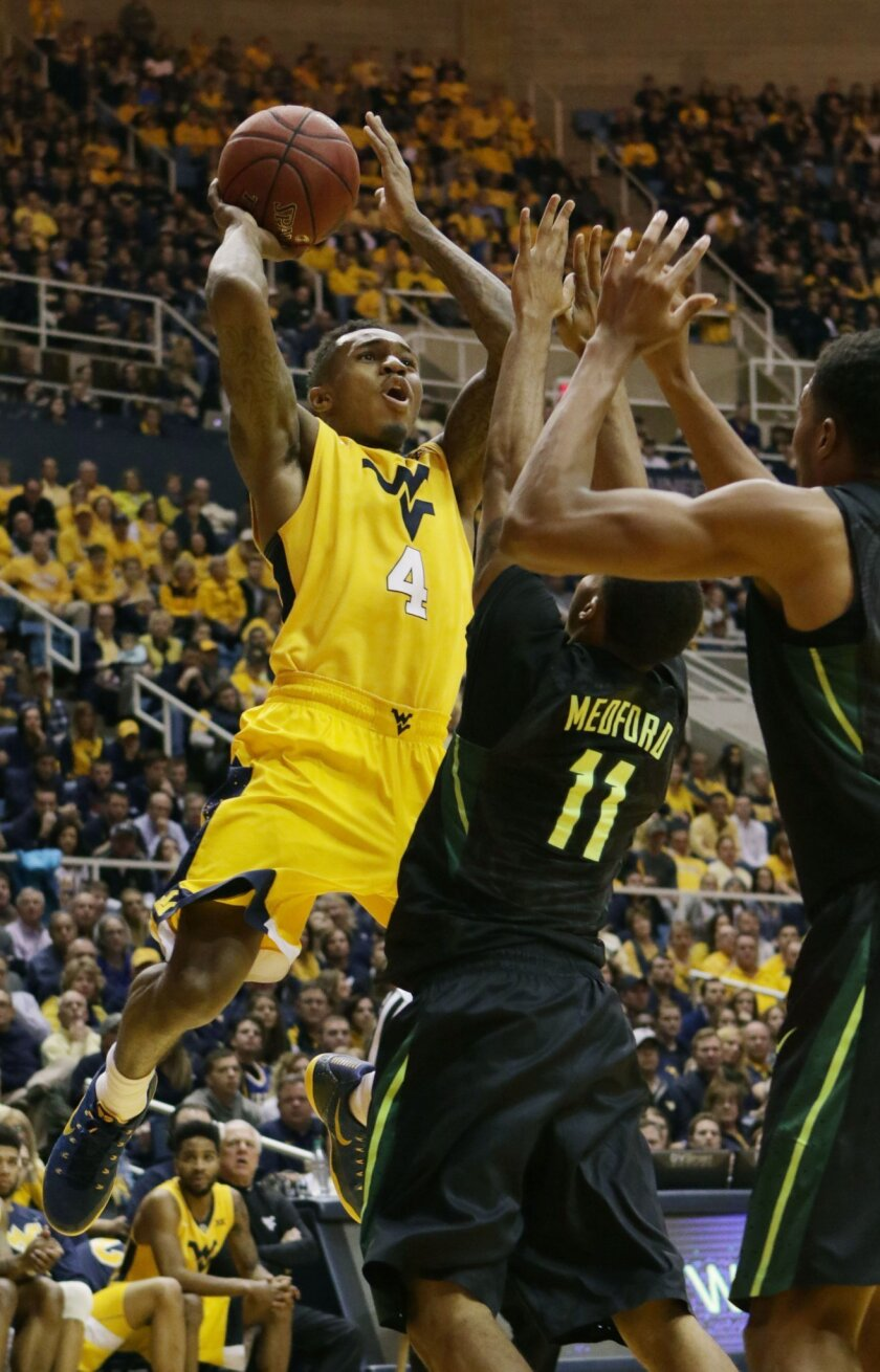 West Virginia guard Daxter Miles Jr. (4) shoots over Baylor guard Lester Medford (11) during the second half of an NCAA college basketball game, Saturday, Feb, 6, 2016, in Morgantown, W.Va. (AP Photo/Raymond Thompson)