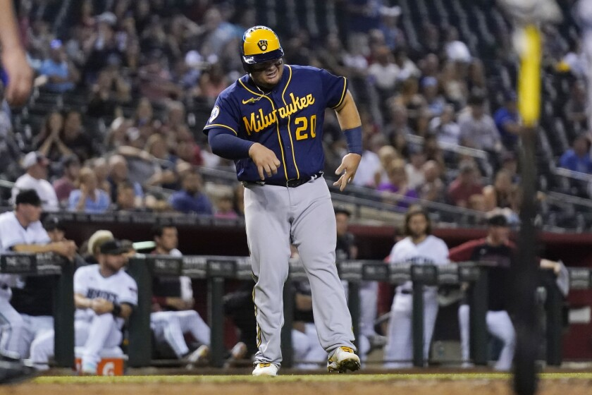An injured Milwaukee Brewers' Daniel Vogelbach limps to home plate to score a run against the Arizona Diamondbacks during the sixth inning of a baseball game Tuesday, June 22, 2021, in Phoenix. (AP Photo/Ross D. Franklin)