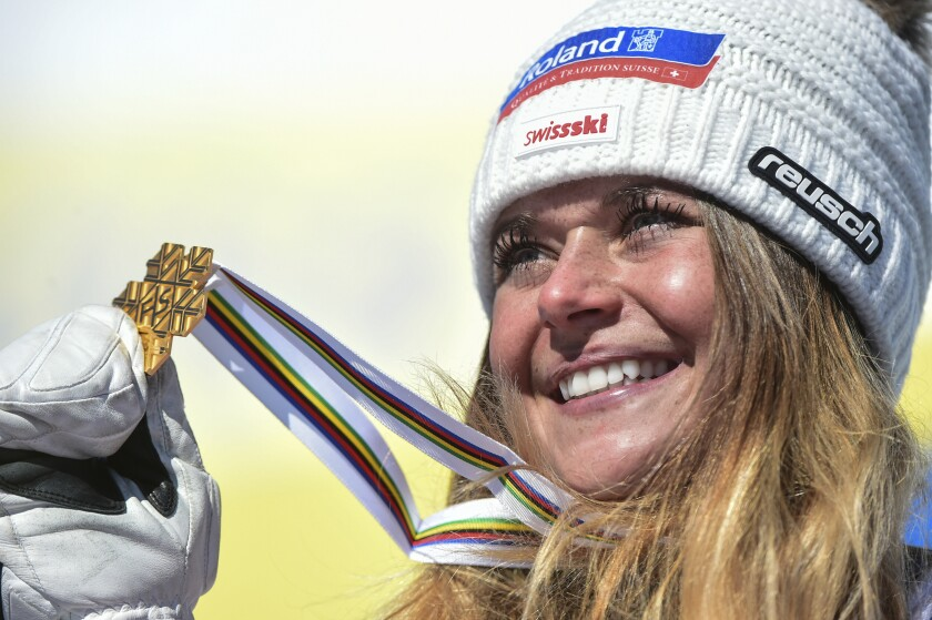 Switzerland's Corinne Suter holds the gold medal on the podium after the women's downhill, at the alpine ski World Championships in Cortina d'Ampezzo, Italy, Saturday, Feb. 13, 2021. (AP Photo/Marco Tacca)