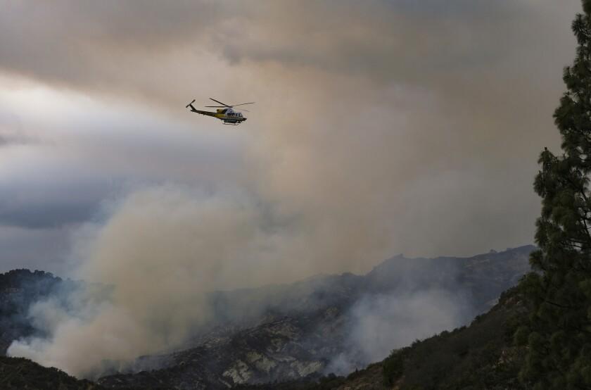 Un helicóptero sobrevuela un incendio forestal en la zona de Pacific Palisades