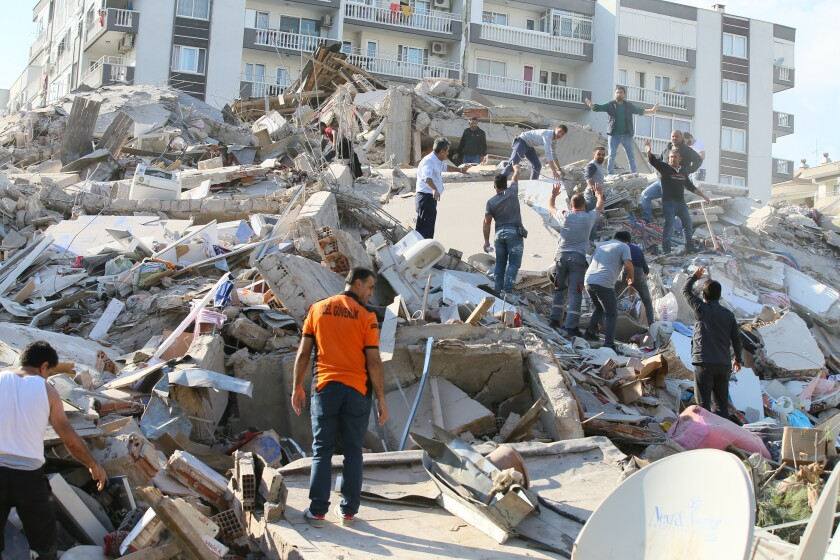 Search and rescue workers look in a collapsed building in the Bayrakli district of Izmir after a strong quake shook Turkey.